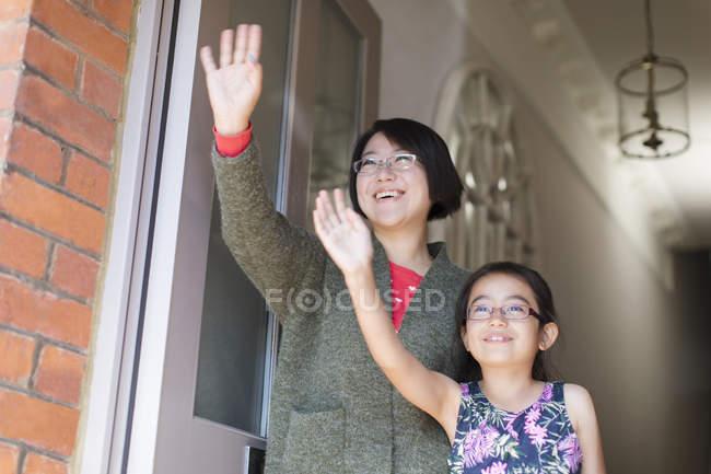 Mother and daughter waving at front door — Foto stock