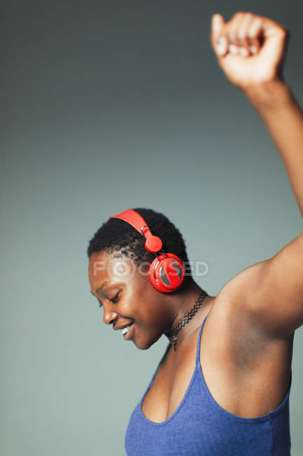 Carefree woman with headphones dancing, listening to music — Stock Photo