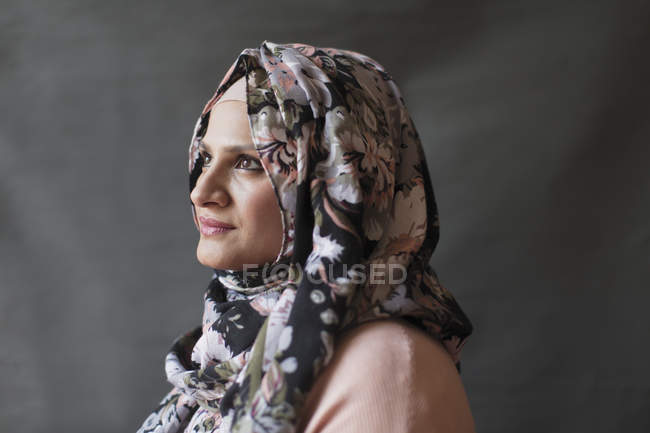 Serene, thoughtful woman wearing floral hijab, looking away — Stock Photo