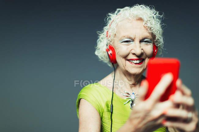 Пожилая женщина с наушниками и mp3-плеером, слушая музыку — стоковое фото