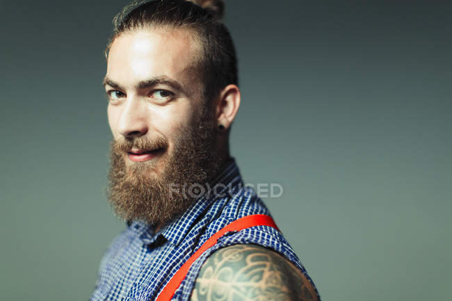 Portrait confident, cool male hipster with beard and shoulder tattoo — Stock Photo