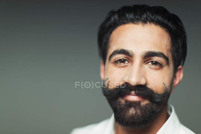 Portrait smiling, confident young man with handlebar handlebar mustache — Stock Photo