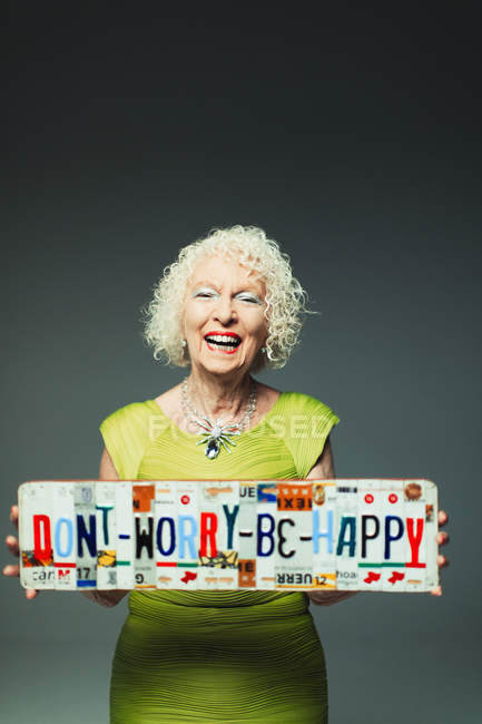 Portrait happy senior woman holding  Dont Worry Be Happy  license plates — Stock Photo