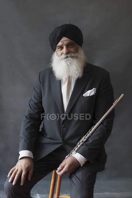 Портрет уверенный, хорошо одетый пожилой человек в тюрбане с флейтой — стоковое фото