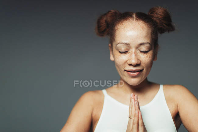 Portrait serene woman with freckles meditating with eyes closed — Stock Photo