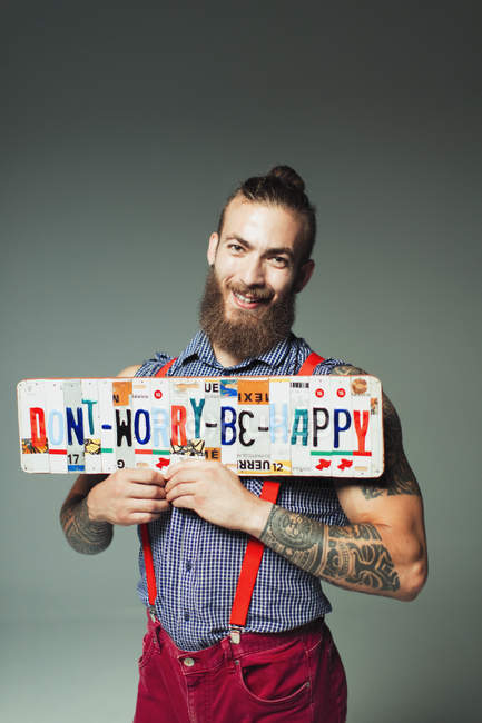 Portrait confident hipster man holding  Dont Worry Be Happy  license plates — Stock Photo