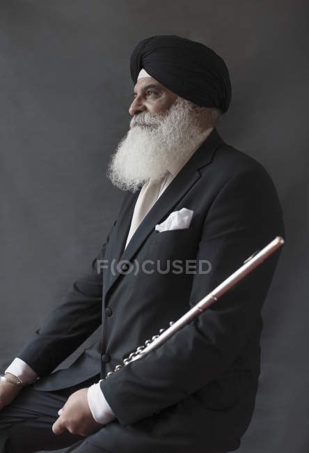 Портрет серьезный, хорошо одетый пожилой человек в тюрбане с флейтой — стоковое фото