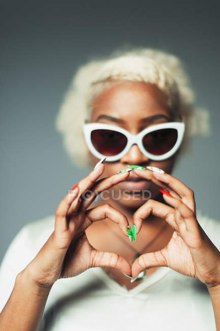 Portrait cool young woman gesturing heart-sign with hands — Stock Photo