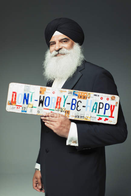 Portrait smiling, well-dressed senior man in turban holding  Dont Worry Be Happy  license plates — Stock Photo