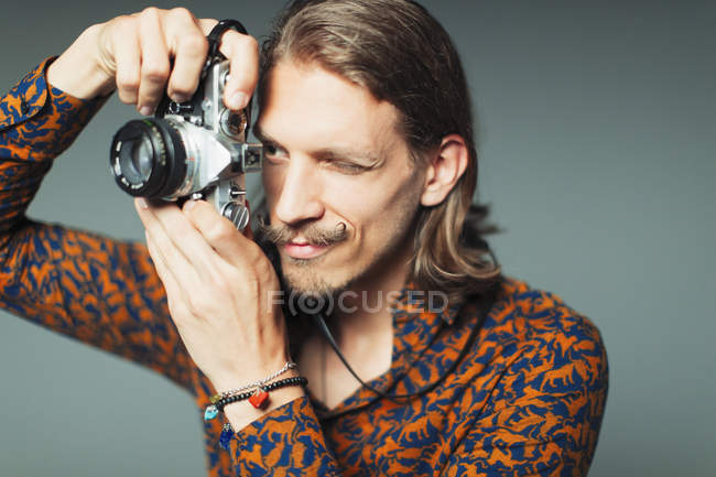 Young man with handlebar mustache using retro camera — Stock Photo