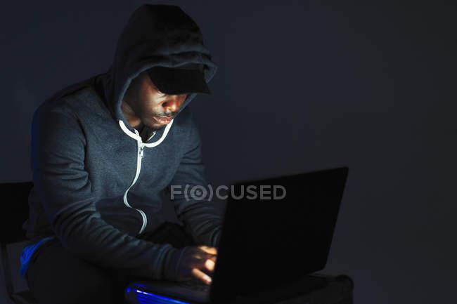 Adolescent garçon dans hoody penché sur portable — Photo de stock