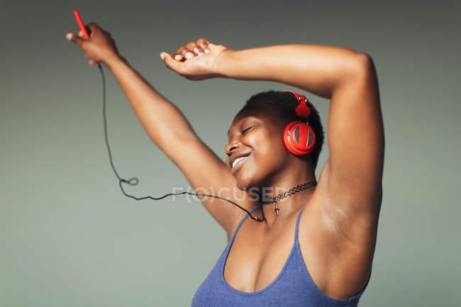 Беззаботная молодая женщина с наушниками и mp3-плеером танцует — стоковое фото