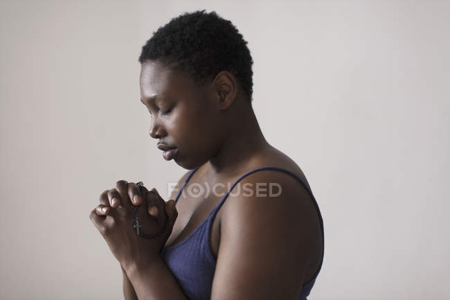 Portrait serene woman with rosary praying — Stockfoto