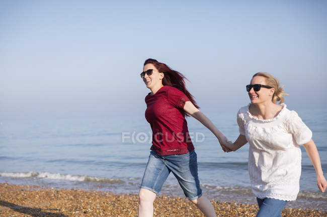 Affectionate lesbian couple holding hands on sunny beach — Stock Photo