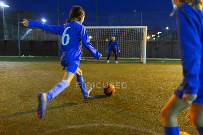 Fußballerin kickt Ball in Richtung Tor — Stockfoto