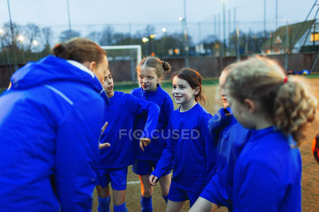 Girls soccer team listening to coach in huddle — Stock Photo