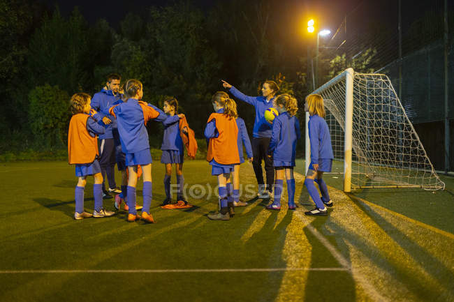 Girls soccer team listening to coaches on field at night — Stock Photo
