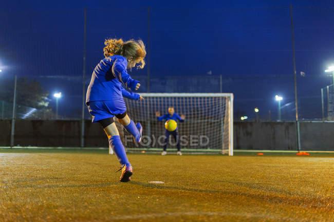 Fußballerin kickt den Ball Richtung Tor — Stockfoto