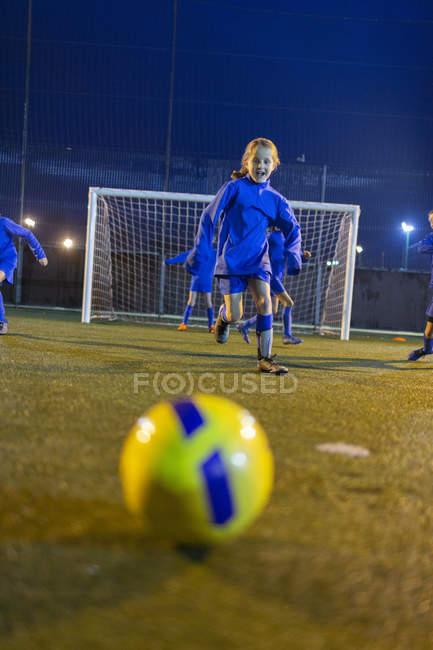 Дівчина футболіста практикувати на поле вночі — стокове фото