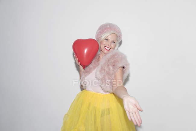 Portrait carefree, playful senior woman with heart-shape balloon — Stock Photo