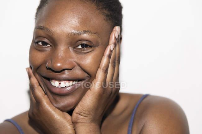 Close up retrato sorridente mulher com a cabeça nas mãos — Fotografia de Stock