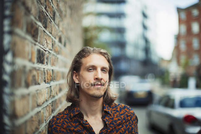 Portrait confident young male hipster on urban sidewalk — Stock Photo