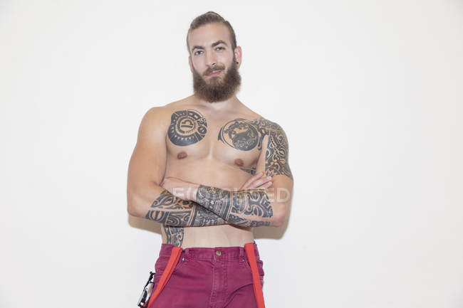 Portrait confident, cool male hipster with bare chest and tattoos — Stockfoto