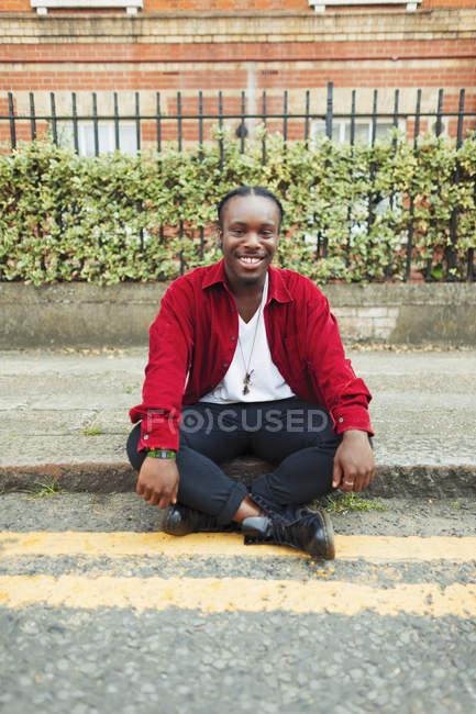 Портрет улыбающийся, уверенный в себе подросток, сидящий на городской обочине — стоковое фото