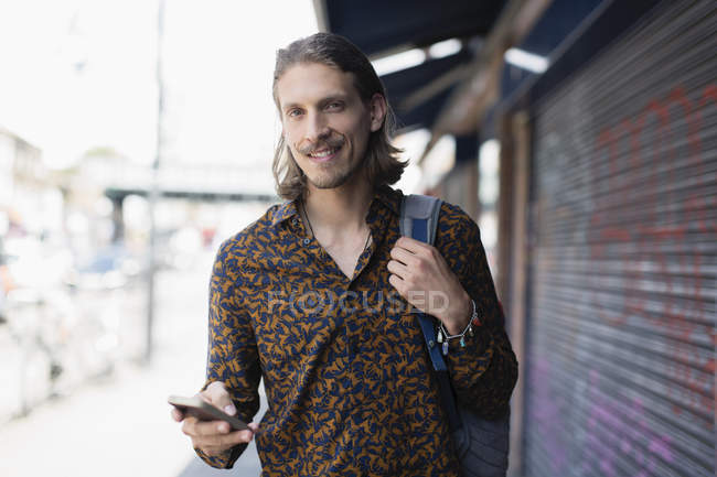 Portrait confident hipster man with smart phone on urban sidewalk — Stock Photo