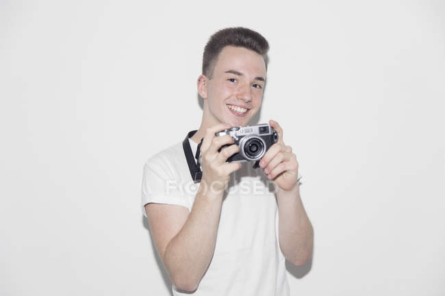 Ritratto sorridente, fiducioso ragazzo adolescente con fotocamera retrò — Foto stock