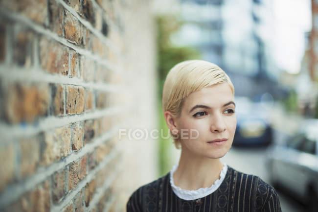 Serena jovem mulher olhando para longe na calçada urbana — Fotografia de Stock