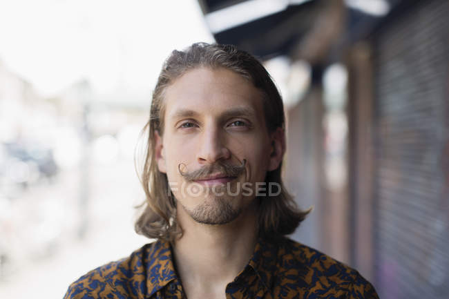 Portrait confident young male hipster with mustache — Stock Photo