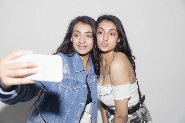 Teenage twin girls taking selfie with smart phone — Stock Photo