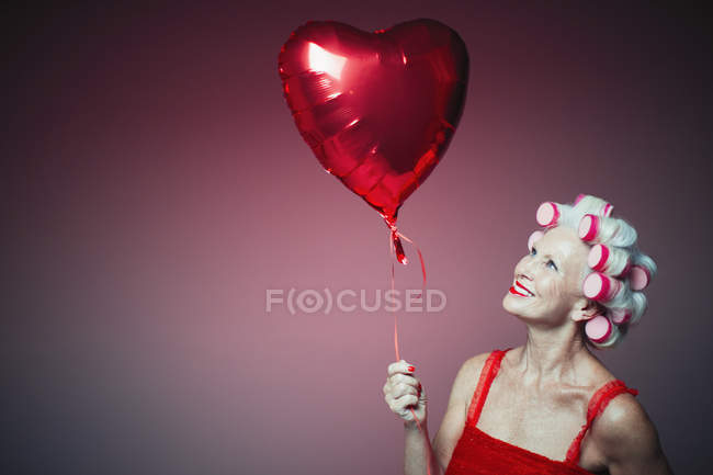 Portrait smiling senior woman with hair in curlers holding heart-shape balloon — Fotografia de Stock