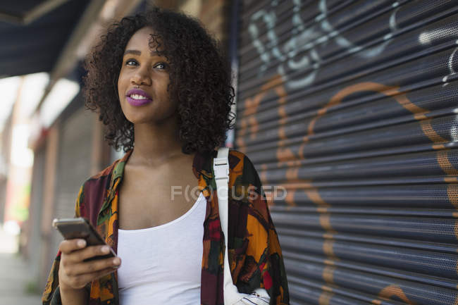 Young woman with smart phone on urban sidewalk — Stock Photo