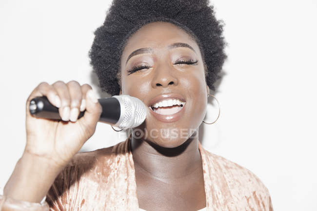 Young woman with microphone singing — Stock Photo