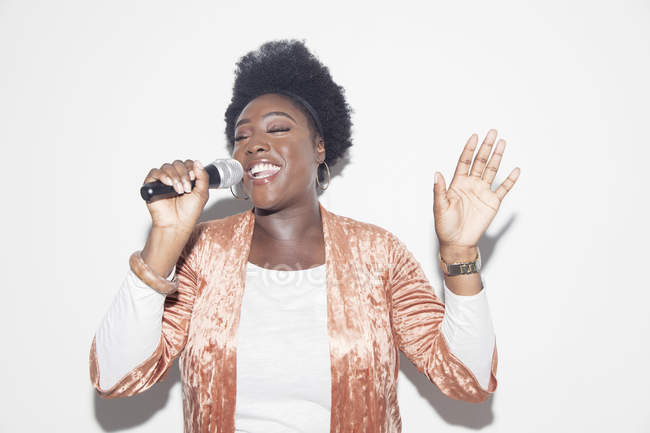 Woman singing with microphone — Stock Photo