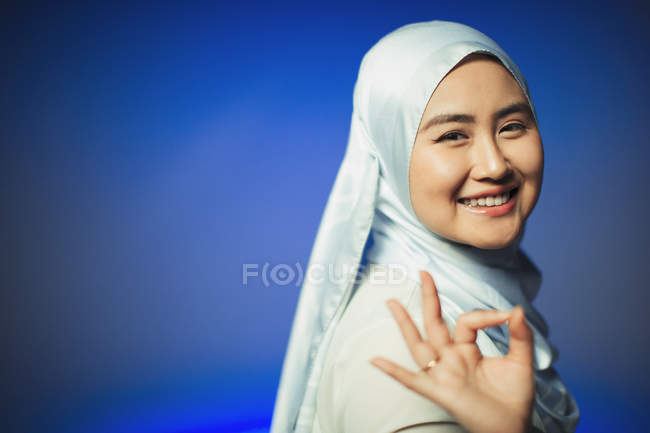 Portrait smiling, confident young woman in hijab gesturing OK — Stock Photo