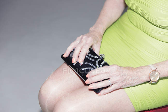 Senior woman in dress holding clutch purse — Stock Photo