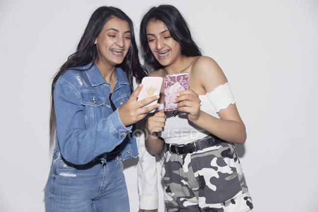 Teenage twin sisters using smart phones — Stock Photo