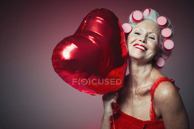 Portrait playful senior woman with hair in curlers holding heart-shape balloon — Stock Photo