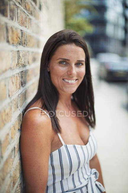 Portrait confident, smiling woman on urban sidewalk — Stock Photo