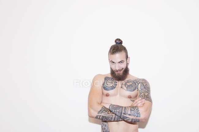Porträt selbstbewusster männlicher Hipster mit nackter Brust und Tattoos — Stockfoto
