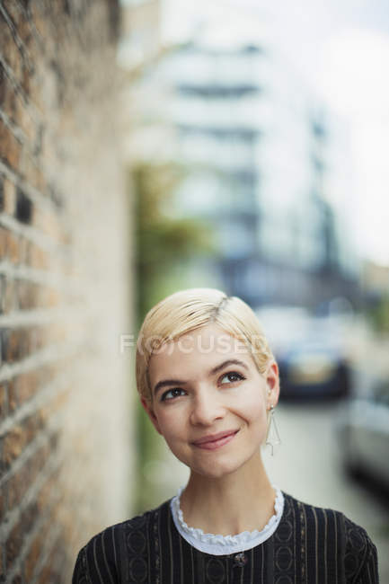 Ritratto giovane donna fiduciosa e curiosa sul marciapiede urbano — Foto stock