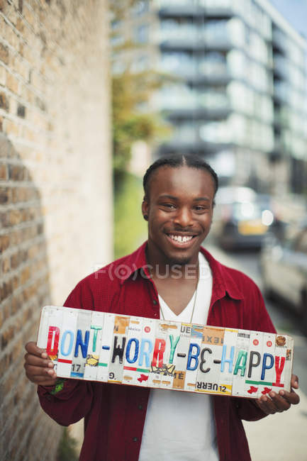 Portrait smiling teenage boy holding  Dont Worry Be Happy  license plates — Stock Photo