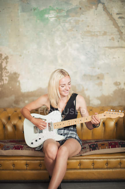 Young woman playing electric guitar on sofa — Stock Photo