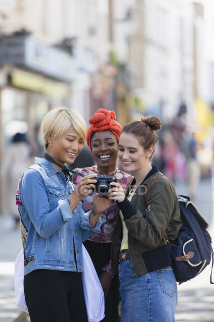 Young women friends using digital camera on urban street — Stock Photo
