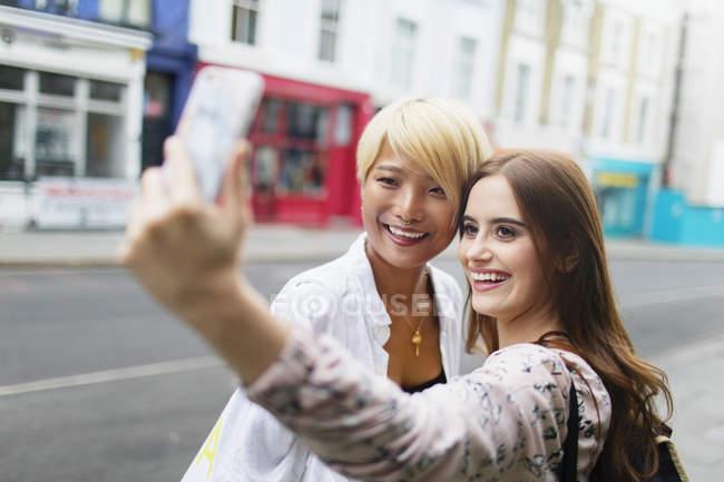 Amis de jeunes femmes prenant selfie avec téléphone intelligent sur l'artère urbaine — Photo de stock