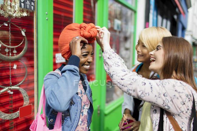 Молодые женщины помогают другу настраивать платки на городской тротуаре — стоковое фото