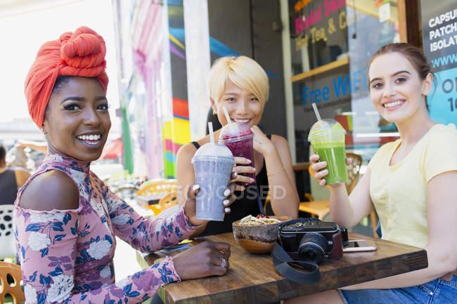Porträt lächelnde junge Freundinnen, die Smoothies im Straßencafé trinken — Stockfoto
